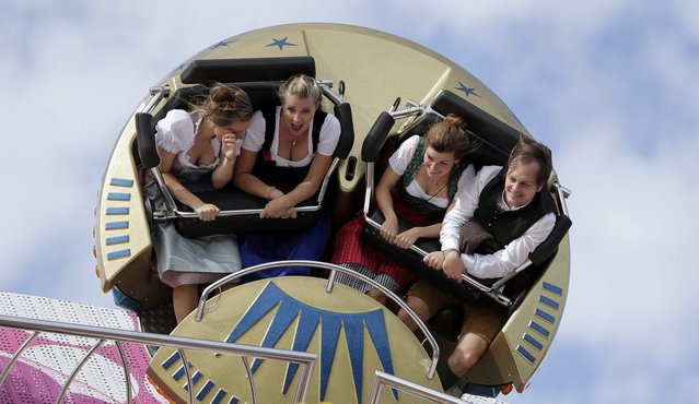 People enjoy a fairground ride at the 181st Oktoberfest beer festival in Munich, southern Germany, Saturday, September 20, 2014. (Photo by Matthias Schrader/AP Photo)