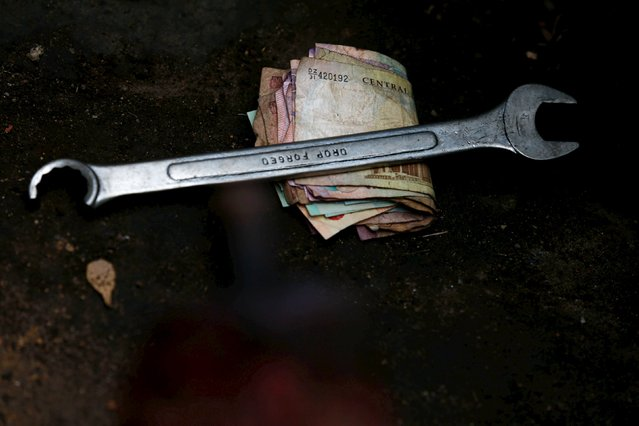A spanner is placed on Nigerian notes during an annual prayer and sacrifice to the iron god Ogun in Abuja, Nigeria June 23, 2015. (Photo by Afolabi Sotunde/Reuters)