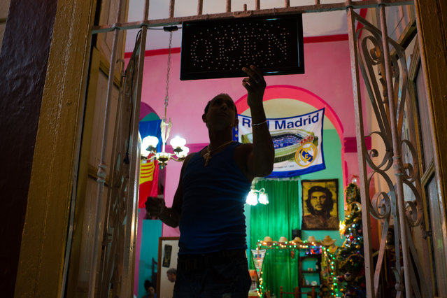 Leonardo Leiva, 45, a restaurant owner in the historic center of Havana, Cuba repairs an open sign in the doorway of his place, Don Pucho, which is named after his father on the night of Thursday January 22, 2015. (Photo by Sarah L. Voisin/The Washington Post)