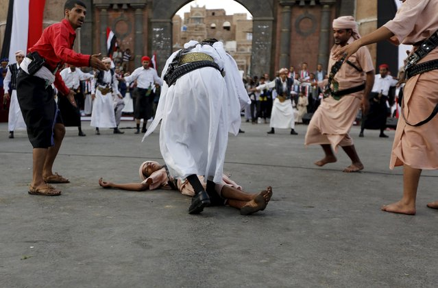 A Houthi follower lies on the ground, resempling a victim, as others perform a war dance during a ceremony marking the first anniversary of the Houthi movement's takeover of Yemen's capital Sanaa September 21, 2015. (Photo by Khaled Abdullah/Reuters)