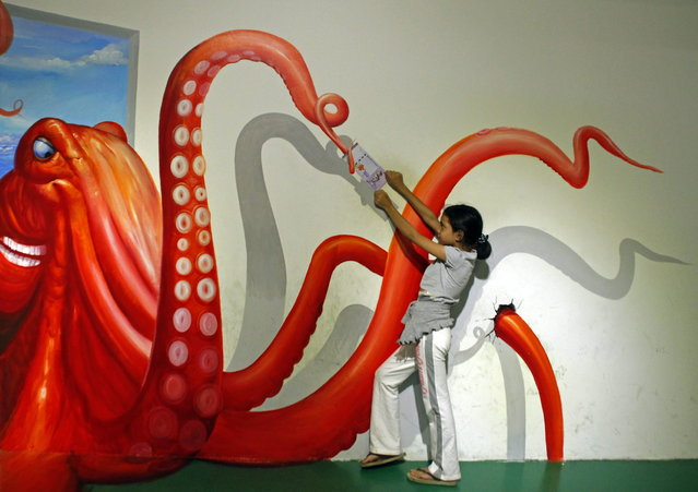 A visitor poses for a photo with a 3D artwork at the Trick Art Museum in Shah Alam, outside Kuala Lumpur, Malaysia, Tuesday, Dec. 4, 2012. (AP Photo/Lai Seng Sin)