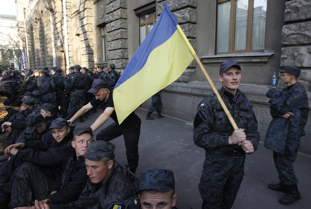 Conscripts of the National Guard of Ukraine gather near the presidential administration headquarters to demand their demobilization in Kiev, October 13, 2014. Several hundred combatants, who took part in military operations in the eastern regions of Ukraine, had served for more than a year, according to participants. (Photo by Valentyn Ogirenko/Reuters)