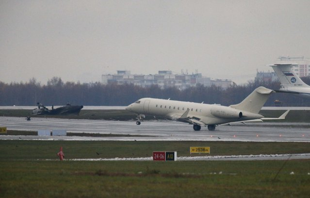 A plane takes off in front of what is believed to be the wreckage of the chief executive of Christophe de Margerie's Dassault Falcon jet at Moscow's Vnukovo airport, October 21, 2014. The chief executive of French oil major Total, Christophe de Margerie, was killed when his private jet collided with a snow plow as it was taking off from Moscow's Vnukovo airport on Monday night. (Photo by Maxim Zmeyev/Reuters)
