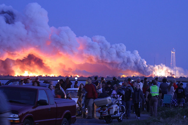 """People who came to watch the launch walk away after an unmanned rocket owned by Orbital Sciences Corporation exploded (background) October 28, 2014 just seconds after lift-off from Wallops Island, Virginia, on what was to be a resupply mission to the International Space Station. """"The Antares rocket suffered an accident shortly after lift-off"""", NASA mission control in Houston said, describing the blast as a """"catastrophic anomaly"""". (Photo by Steve Alexander/AFP Photo)"""