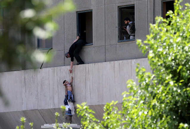 A boy is evacuated during an attack on the Iranian parliament in central Tehran, Iran, June 7, 2017. (Photo by Omid Vahabzadeh/Reuters/TIMA)