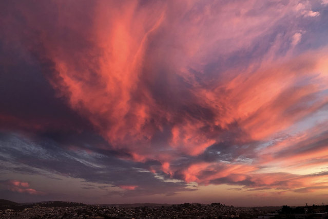 Clouds are shown over San Francisco as the sun sets, Friday, July 10, 2020. (Photo by Jeff Chiu/AP Photo)