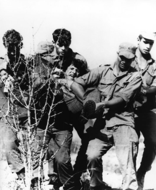 Israeli troops carry a squatter from a site near Joricho north of the Dead Sea in the occupied West Bank of Jordan on Wednesday, October 9, 1974. Rightwing groups attempted to establish settlement in the area in advance of U.S. Secretary of State Henry Kissinger's visit. The squatters hoped to influence possible negotiations of territory with Jordanians. (Photo by Max Nash/AP Photo)