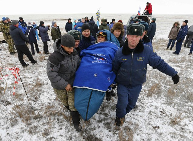Ground personnel carry International Space Station (ISS) crew member Maxim Suraev of Russia shortly after landing near the town of Arkalyk in northern Kazakhstan November 10, 2014. (Photo by Shamil Zhumatov/Reuters)