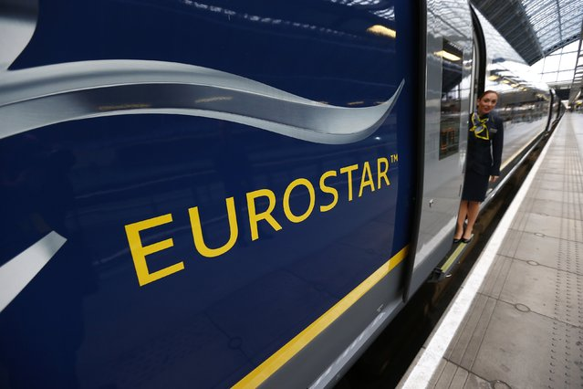 A Eurostar employee poses with their new Siemens e320 train at St Pancras station in central London, November 13, 2014. (Photo by Andrew Winning/Reuters)