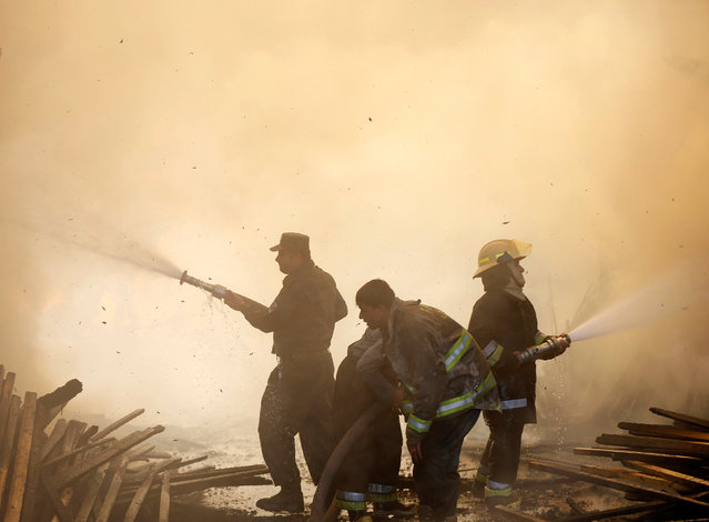 Afghan firefighters try to extinguish a fire which broke out at a wood market in Kabul, Afghanistan September 18, 2016. (Photo by Omar Sobhani/Reuters)