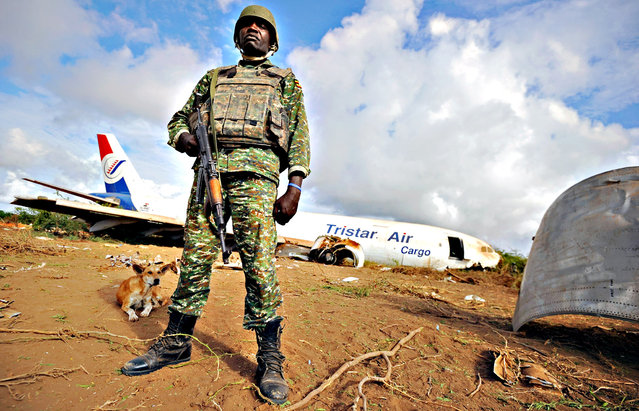 A soldier from the African Union (AU) peacekeeping force stands guard at the site where a cargo plane carrying supplies for AU troops crash-landed outside Somalia's capital, on October 13, 2015 at Abirska, some 18 kilometres outside Somalian capital, Mogadishu. The officials said the Egyptian-owned transport plane went down after making several unsuccessful passes over the seafront airport. (Photo by Mohamed Abdiwahab/AFP Photo)
