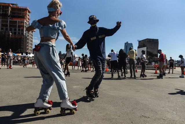 """People roller skate during a """"pop-up"""" roller skating session on September 5, 2020 in the Brooklyn borough of New York City. Outdoor roller skating has gained in popularity since restrictions on indoor activities were restricted due to the coronavirus (COVID-19) pandemic. (Photo by Stephanie Keith/Getty Images)"""