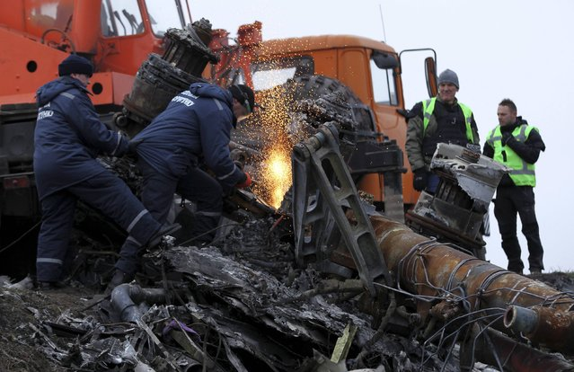Local workers cut wreckage of the Malaysia Airlines Boeing 777 plane (flight MH17) at the site of the plane crash near the settlement of Grabovo in the Donetsk region November 16, 2014. (Photo by Antonio Bronic/Reuters)