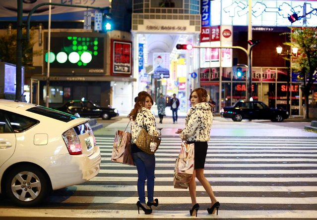 Women carry shopping bags in the Dotonbori amusement district of Osaka, western Japan November 19, 2014. (Photo by Thomas Peter/Reuters)