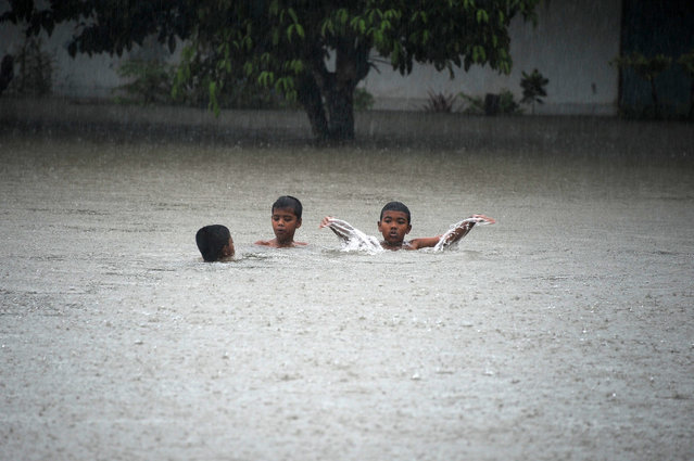 Boys play in flood waters in a school during heavy rain fall, as floods hit parts of Thailand's restive southern province of Narathiwat. Thailand's southernmost provinces near the Malaysian border suffer almost daily gun and bomb attacks by shadowy insurgents fighting for greater autonomy. (Photo by Madaree Tohlala)