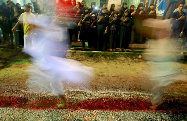 Shi'ite Muslims walk on hot coals at a ceremony during the Ashura festival at a mosque in central Yangon October 21, 2015. (Photo by Soe Zeya Tun/Reuters)