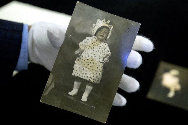 Martin Nolan, Executive Director of Julien's Auctions, holds a photograph of actress Marilyn Monroe at age 2 during an exhibition of Monroe's personal effects in Beijing, Tuesday, September 27, 2016. Clothing, handwritten notes, and dozens of other personal items that the iconic actress left to a friend and mentor were in Beijing on Tuesday for a private viewing by Chinese collectors before being auctioned in Los Angeles in November. (Photo by Mark Schiefelbein/AP Photo)