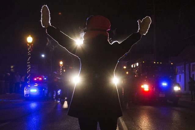 A female protester raises her hands while blocking police cars in Ferguson, Missouri, November 25, 2014. More than 2,000 National Guard troops spread out across the St. Louis area on Tuesday to prevent another night of rioting and looting after a grand jury declined to indict Darren Wilson, a white police officer, in the August shooting of unarmed black teenager Michael Brown. (Photo by Adrees Latif/Reuters)