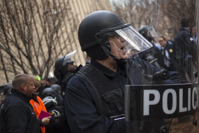 Police in riot gear ask protesters, who were demanding justice for Michael Brown, to stay back as they make arrests for disrupting traffic near the Edward Jones Dome, the site of an NFL football game between the St. Louis Rams and the Oakland Raiders, in downtown St. Louis, Missouri November 30, 2014. (Photo by Adrees Latif/Reuters)