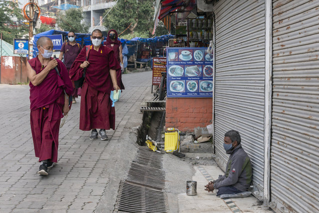 Exile Tibetan Buddhist monks wearing masks as a precautionary measure against the coronavirus walk past a man begging in Dharmsala, India, Tuesday, October 13, 2020. (Photo by Ashwini Bhatia/AP Photo)