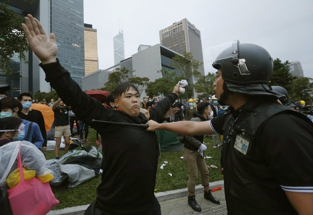 A pro-democracy protester blocks a riot policeman during a clash outside the government headquarters in Hong Kong December 1, 2014. (Photo by Bobby Yip/Reuters)