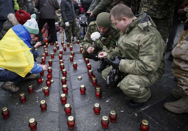 "Servicemen of ""Kiev 12"" military defence battalion light candles to honour the memory of their dead comrades after a welcoming ceremony in central Ukrainian capital Kiev December 6, 2014. (Photo by Gleb Garanich/Reuters)"