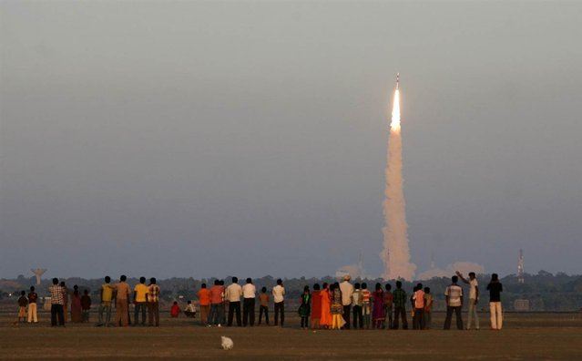 Onlookers watch as the Indian Space Research Organization's Polar Satellite Launch Vehicle (PSLV-C20) lifts off from the Satish Dhawan Space Center in Sriharikota, India, on February 25, 2013. The rocket successfully launched the SARAL oceanographic satellite and six other spacecraft. (Photo by Arun Sankar K./AP Photo)