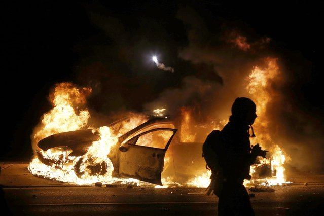 A police car burns on the street after a grand jury returned no indictment in the shooting of Michael Brown in Ferguson, Missouri November 24, 2014. Gunshots were heard and bottles were thrown as anger rippled through a crowd outside the Ferguson Police Department in suburban St. Louis after authorities on Monday announced that a grand jury voted not to indict a white officer in the August shooting death of an unarmed black teen. (Photo by Jim Young/Reuters)
