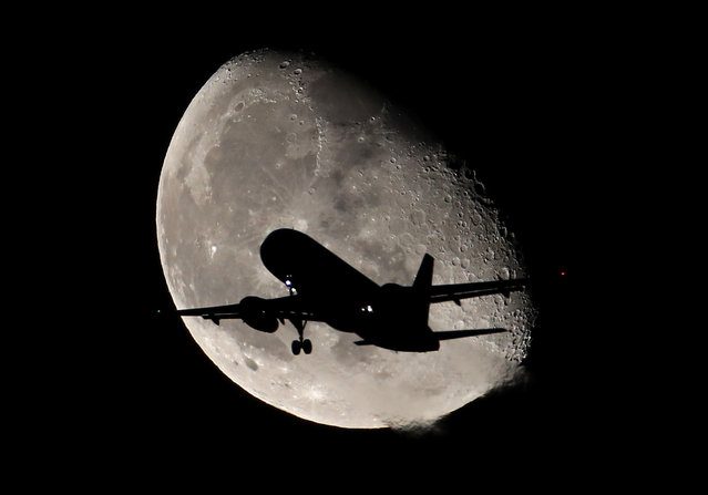 A plane prepares to land at Heathrow Airport with the moon behind it on November 05, 2020 in London, England. (Photo by Chris Jackson/Getty Images)