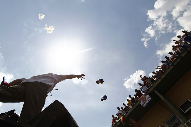 Venezuela's opposition leader and presidential candidate Henrique Capriles throws his cap to supporters during a campaign rally in the state of Guarico April 8, 2013. Venezuelans will hold presidential elections on April 14. (Photo by Carlos Garcia Rawlins/Reuters)