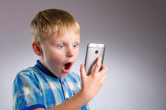 Shocking technology. Young boy looking shocked with smartphone. (Photo by Derek Northrop/Getty Images)