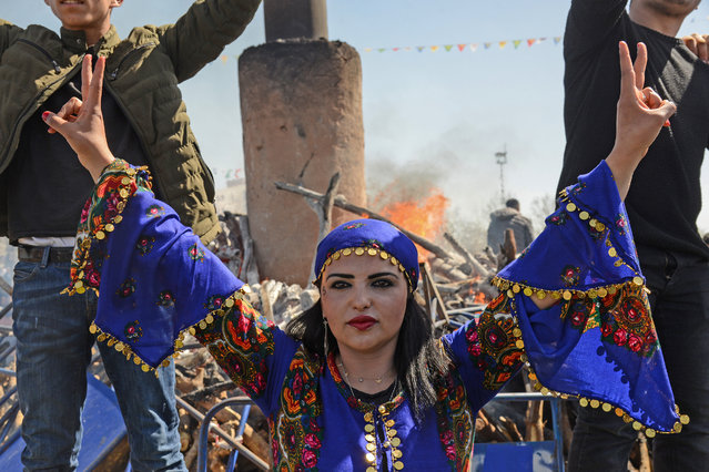 A young woman flashes the victory sign in front of a bonfire as Turkish Kurds gather during Newroz celebrations for the new year in Diyarbakir, southeastern Turkey, on March 21, 2018. Newroz (also known as Nawroz or Nowruz) is an ancient Persian festival, which is also celebrated by Kurdish people, marking the first day of spring, which falls on March 21. (Photo by Ilyas Akengin/AFP Photo)