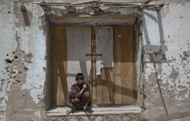 In this August 18, 2016 photo, a teenager sits next to a closed shop, in Qazideh village, Wakhan district of Badakhshan province, far northeastern Afghanistan. (Photo by Massoud Hossaini/AP Photos)