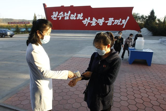Hygienic and anti-epidemic officials disinfect and check the temperature of people outside the entrance to Songdowon General Foodstuff Factory in the city of Wonsan, Kangwon Province, North Korea DPRK, on Wednesday, October 28, 2020. (Photo by Jon Chol Jin/AP Photo)