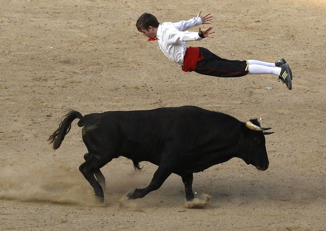 A Spanish recortador jumps over a bull during a show in Cali December 21, 2014. (Photo by Jaime Saldarriaga/Reuters)