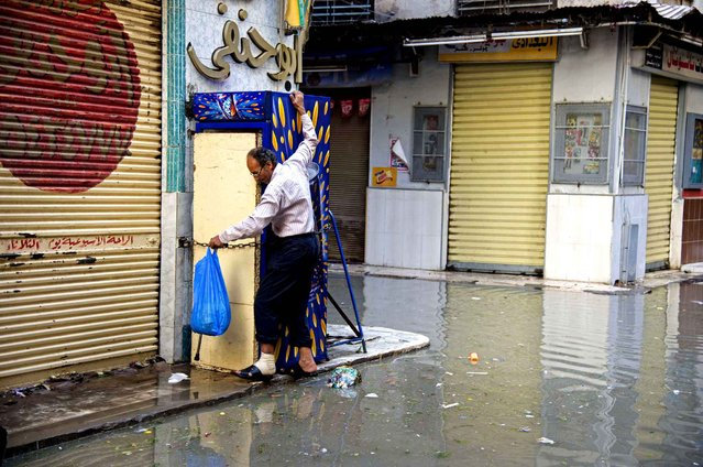 An Egyptian man walks around a flooded street after a heavy rainfall in the coastal city of Alexandria, Egypt, Sunday, October 25, 2015. Severe weather swept across the Middle East on Sunday, pounding Israel with baseball-sized hail, sending torrents of uncollected garbage through the streets of Beirut and killing six people in Egypt, five of whom were electrocuted by a fallen power cable. (Photo by Heba Khamis/AP Photo)