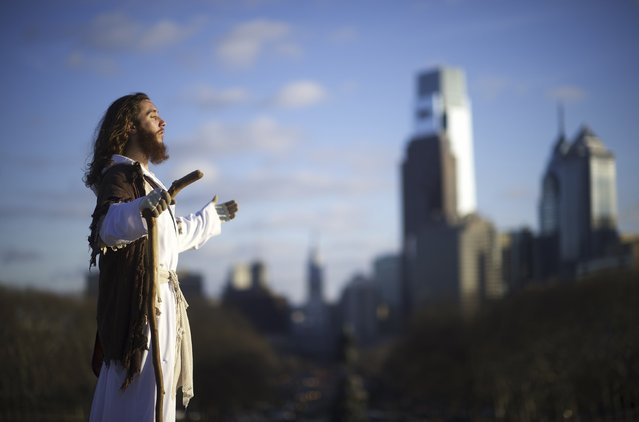 "With the Philadelphia skyline behind him, Michael Grant, 28, ""Philly Jesus"", looks towards the afternoon sun on December 18, 2014. Nearly everyday for the last 8 months, Grant has dressed as Jesus Christ, and walked the streets of Philadelphia to share the Christian gospel by example. (Photo by Mark Makela/Reuters)"