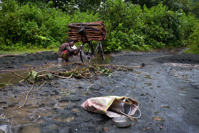 In this September 10, 2014 photo, a man washes his bicycle sitting on loose asbestos sediments brought down by a stream from Roro hills in Roro, India. (Photo by Saurabh Das/AP Photo)