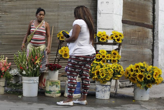 A woman offers flowers for sale along a street in Havana December 23, 2014. (Photo by Enrique De La Osa/Reuters)