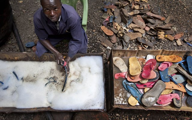 In this photo taken Monday, April 29, 2013, a worker washes and scrubs discarded flip-flops prior to them being sorted and carved into toy animals, at the Ocean Sole flip-flop recycling company in Nairobi, Kenya. The company is cleaning the East African country's beaches of used, washed-up flip-flops and the dirty pieces of rubber that were once cruising the Indian Ocean's currents are now being turned into colorful handmade giraffes, elephants and other toy animals. (Photo by Ben Curtis/AP Photo)