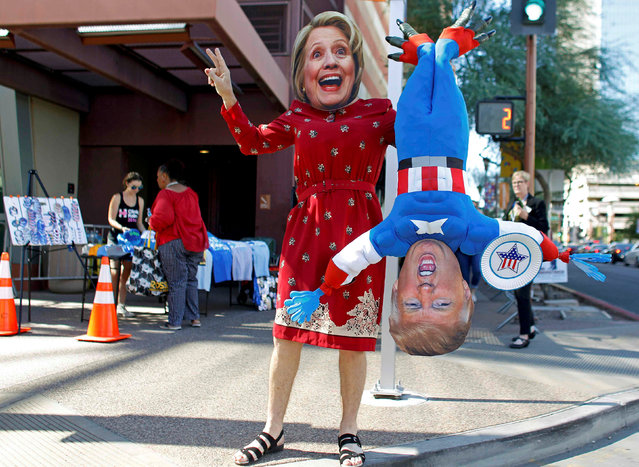 A man wears a mask depicting Democratic U.S. presidential candidate Hillary Clinton while holding a doll depicting Republican presidential nominee Donald Trump in Phoenix, Arizona October 20, 2016. (Photo by Ricardo Arduengo/Reuters)