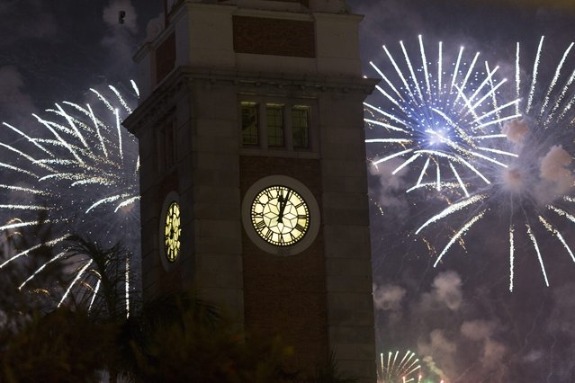 Fireworks explode behind the Clock Tower to celebrate the New Year in Tsim Sha Tsui, Hong Kong, China, 31 December 2014. In Hong Kong, a British colony for more than 150 years, a large fireworks display lasting eight minutes lit up Victoria Harbour for New Year's Eve. (Photo by Jerome Favre/EPA)