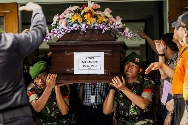 Indonesian Army carry the coffin of Kevin Alexander Soetjipto, a victim of the AirAsia flight QZ8501, after he was handed over to his family at the police hospital on January 2, 2015 in Surabaya, Indonesia. A massive recovery operation has begun following confirmation from Indonesian officials that remains and debris found in waters off Borneo are from the missing AirAsia plane. Flight QZ8501 from Surabaya to Singapore, with 162 people on board, lost contact with air traffic control at 07:24 a.m. local time on December 28.  (Photo by Oscar Siagian/Getty Images)
