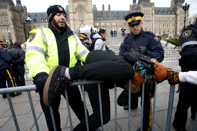 A protestor struggles to cross a police barricade during a demonstration against the proposed Kinder Morgan pipeline on Parliament Hill in Ottawa, Ontario, Canada, October 24, 2016. (Photo by Chris Wattie/Reuters)
