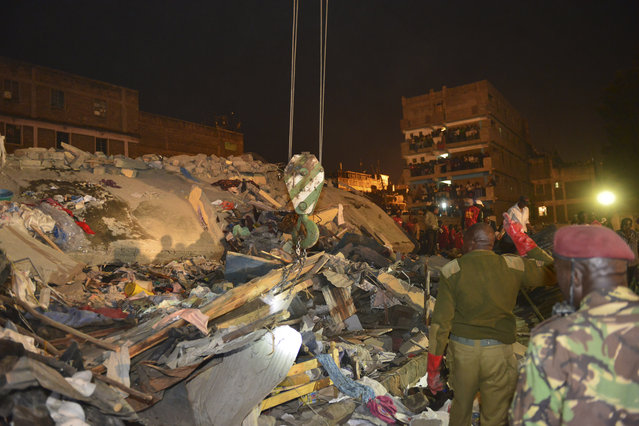 Kenya Para military soldiers watch cranes removing debris as they search for survivors of a multi-storey building collapse  in the capital Nairobi, Kenya Sunday, January 4, 2015. (Photo by AP Photo)