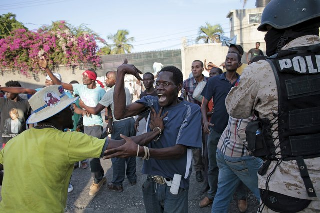 A protester controls another one as he provokes residents during a demonstration against the results of the presidential elections in Port-au-Prince, Haiti, November 24, 2015. (Photo by Andres Martinez Casares/Reuters)