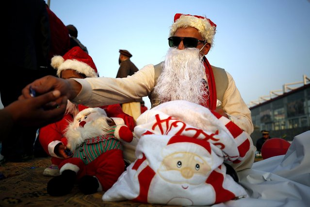 A Christian in a Santa Claus suit distributes sweets during an event to celebrate Christmas, in Islamabad, Pakistan, Tuesday, December 1, 2020. Although Pakistani Christians are in the minority, Christmas is a national holiday and is observed across the country as an occasion to celebrate. (Photo by Anjum Naveed/AP Photo)