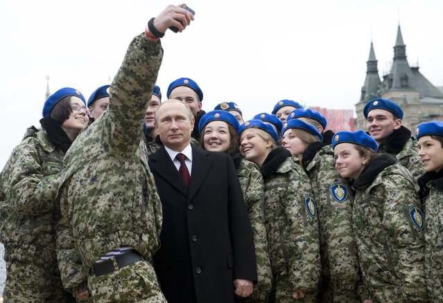 """Vladimir Putin poses for a selfie with members of the youth military patriotic club """"Vympel"""" (The Pennant) during a flower-laying ceremony at a monument of Minin and Pozharsky, the leaders of a liberation struggle against foreign invaders in 1612, on National Unity Day in Red Square in Moscow, Russia November 4, 2015. (Photo by Natalia Kolesnikova/Reuters)"""