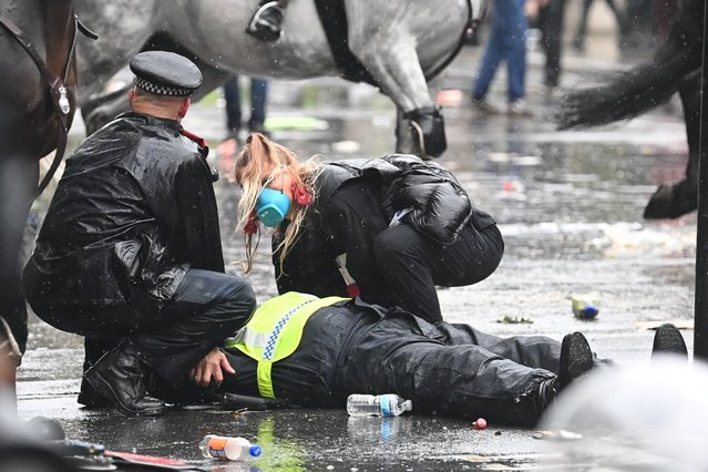 A colleague attends to a police officer who was injured when falling of a horse during scuffles with demonstrators at Downing Street during a Black Lives Matter march in London, Saturday, June 6, 2020, as people protest against the killing of George Floyd by police officers in Minneapolis, USA. Floyd, a black man, died after he was restrained by Minneapolis police while in custody on May 25 in Minnesota. (Photo by London News Pictures)