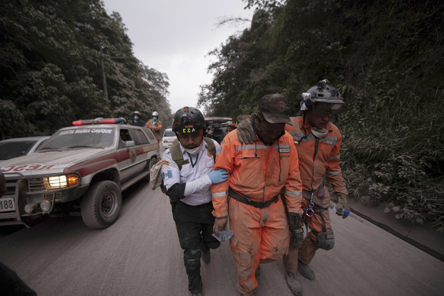 Firefighters leave the evacuation area near Volcan de Fuego, or Volcano of Fire, in El Rodeo, Guatemala, Sunday, June 3, 2018. One of Central America's most active volcanos erupted in fiery explosions of ash and molten rock Sunday, killing people and injuring many others while a towering cloud of smoke blanketed nearby villages in heavy ash. (Photo by Santiago Billy/AP Photo)